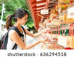 woman hanging the wishes in... | Shutterstock . vector #636294518