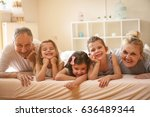 grandparents lying on bed with... | Shutterstock . vector #636489344