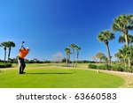 golfer teeing off on beautiful florida course - stock photo