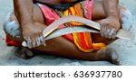 Small photo of Yugambeh Aboriginal man sitting on the ground and holding boomerangs on Aboriginal cultural show in Queensland, Australia.