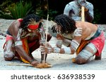 Small photo of Group of Yugambeh Aboriginal warriors men demonstrate fire making craft during Aboriginal culture show in Queensland, Australia.