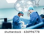 Team of surgeons operating in...