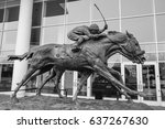 """Small photo of ARLINGTON HEIGHTS, IL - APRIL 29, 2017: Side view of """"Against All Odds,"""" a statue of two horses and jockeys neck and neck in a celebrated inaugural race in 1981 at Arlington International Racecourse."""