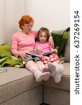 Small photo of child and granny read book together. They sit on couch with plaid, book is on their knees, granny read book aloud for girl