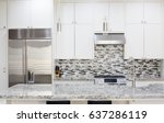 Stock photo snapshot of interior modern kitchen with granite countertop island and smart refrigerator 637286119