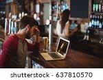 upset man using laptop at bar... | Shutterstock . vector #637810570