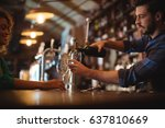 Stock photo male bar tender pouring wine in glasses at bar counter 637810669