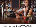 Stock photo female bartender pouring cocktail drink in the glass at bar counter 637840066
