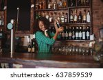 Stock photo female bartender mixing a cocktail drink in cocktail shaker at counter 637859539