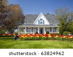A house with large flower beds full of tulips. - stock photo