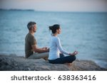 couple practicing yoga at...
