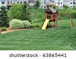 Back Yard Wooden Swing Set on Green Lawn - stock photo