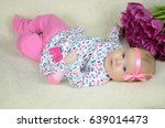 infant with pink tulips | Shutterstock . vector #639014473