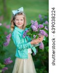 Small photo of Cute stylish dressed young girl lady in blue jeans coat with blond hair and fairy airy skirt close to lilac bush.