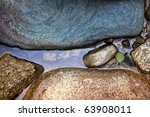 body of water between gentle colored stones with one tiny green leaf. - stock photo