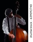 Small photo of Stylish man in shadow playing contrabass, close-up. Wearing plaid flat cap, white shirt and suspenders, black background. Jazz, swing, blues, soul music.