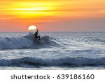 A Surfer Rides A Wave During...