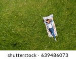 Young Woman Lying On A Rug On...