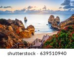 Small photo of beautiful Atlantic ocean view horizon with sandy beach, rocks and waves at sunrise. Algarve, Portugal