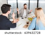 Small photo of Active office worker is sitting afore his co-workers and speaking about certain case. He holding colorful ball