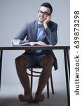 Small photo of Young businessman with bare feet works in office. (Boss, business, rules, officialdom concept)
