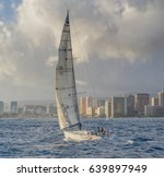 Small photo of Honolulu, Hawaii, USA, May 14, 2017: Speedy white sailboat sailing along the shore line of Waikiki with the island of Oahu in the backdrop.