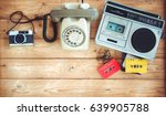 Small photo of Top view hero header - retro technology of radio cassette recorder with retro tape cassette, vintage telephone and film camera on wood table. Vintage color effect styles.