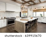Small photo of Kitchen Interior with Island, Sink, Cabinets, and Hardwood Floors in New Luxury Home. Features Elegant Pendant Light Fixtures, and Farmhouse Sink next to Window