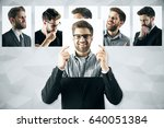 Small photo of Young european man hiding himself behind poster with smiling face. Row of faces with different expressions in the background. Emotion concept