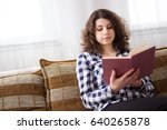 young brunette sitting on bed...   Shutterstock . vector #640265878