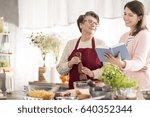 happy grandma cooking with her... | Shutterstock . vector #640352344