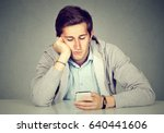 Stock photo bored man using his smart phone 640441606