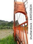Small photo of Vang Vieng, Laos-October 13, 2015: Local motorboat crosses under the red lead painted toll footbridge-Nam Song river linking the left-E.-road bank with the Tham Jang or Chang cave on the right-W.bank.