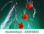 a few whole juicy bright red tomatoes in jets of water on a green background - stock photo