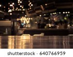 Stock photo wood table top with reflect on blur of lighting in night cafe restaurant background selective focus 640766959