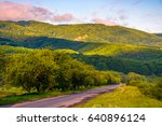 Empty asphalt countryside road in mountains. Serene springtime sunrise with pink light. Blue sky with some clouds - stock photo