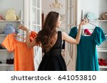 Stock photo image of young lady standing in clothes shop indoors choosing dresses looking aside 641053810