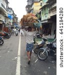 Small photo of Mumbai, India - July 30, 2016 : A man carrying bamboo basket containing goods over his head walking along narrow ally with shop houses on both side of Muslim community
