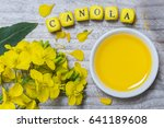 Small photo of Canola with oil concept on gray wood.