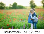 Small photo of Children's love, a little boy and a girl, amicably spend time, laugh and smile, and kiss in the flowering field of poppies