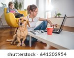 Stock photo small yellow dog sitting on the floor by the woman who is petting him at home 641203954