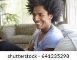 smiling man sitting on sofa in...   Shutterstock . vector #641235298