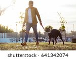 Stock photo portrait of handsome young man with his dog walking in the park 641342074