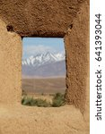 Small photo of The view of atlas mountain chain through a window of a kasbah