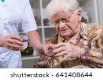 nurse giving medication to an... | Shutterstock . vector #641408644