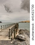 Small photo of Bay of Islands, New Zealand - March 7, 2017: Exit to Tasman Sea from Hokianga Harbour shows large dune and pier pointing at entrance all under heavy cloudscape because of approaching cyclone.