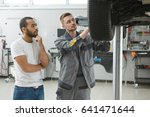 mechanic and car owner looking... | Shutterstock . vector #641471644