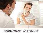 handsome man shaving in bathroom   Shutterstock . vector #641739019