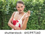 Small photo of Portrait of Asian trans woman or trans gender smoking cigarette in garden. People, smoking and bad habits concept