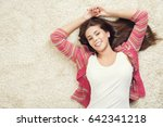Small photo of Woman Lying Down on Carpet, Happy Young Adult Girl Lie on Floor Top View